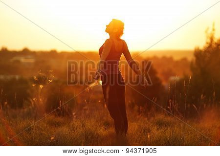 Happy Woman In A Field At Sunset