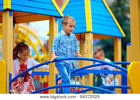 Group Of Playful Kids Having Fun On Toy Castle, On Playground