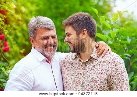 Portrait Of Happy Father And Son Talking Outdoors. Like Father Like Son
