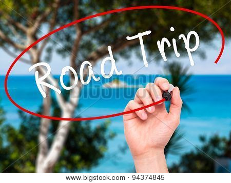 Man Hand writing Road Trip with black marker on visual screen.