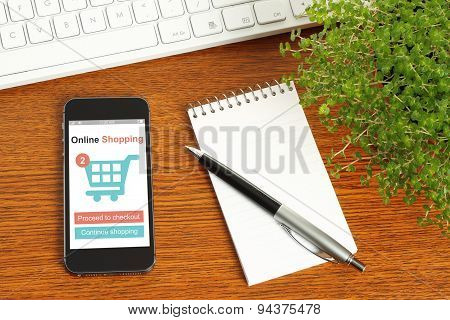 Smart phone with online shopping concept keyboard notepad pen and green plant