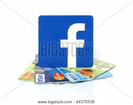 KIEV UKRAINE - MARCH 21 2015: Facebook logo printed on paper and placed on cards Visa and MasterCard