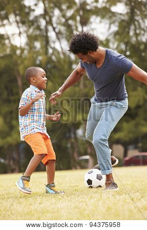 Father With Son Playing Soccer In Park Together