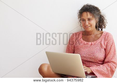 Mature Woman Sitting Against Wall Using Laptop