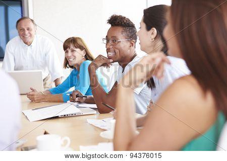 Casually Dressed Businesspeople Having Meeting In Boardroom