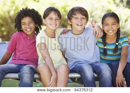 Group Of Children Sitting On Edge Of Trampoline Together