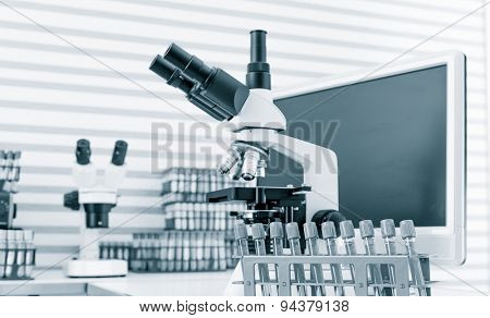 Green liquid in the test tubes in laboratory with microscope.