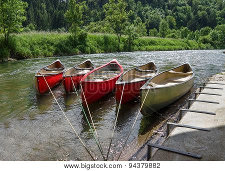 Tied canoes in a river