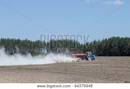 The Tractor Is Spraying Fertilizer In A Field