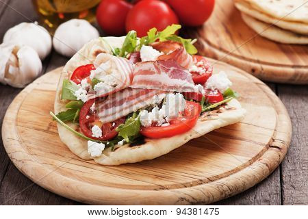 Piadina romagnola, italian flatbread sandwich with rocket salad, ricotta cheese and pancetta bacon