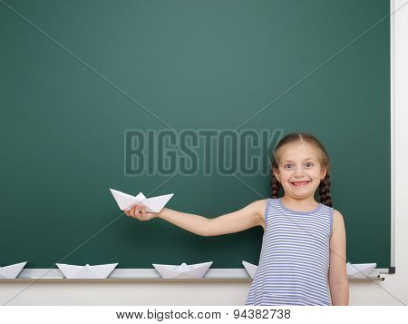 Schoolgirl with origami ship near the school board