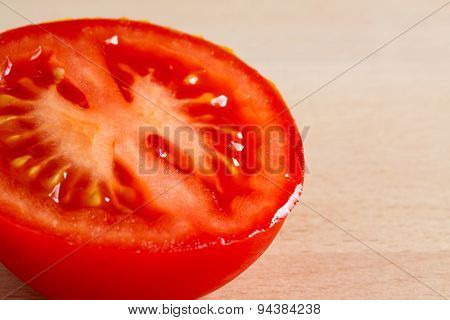 Half of a red ripe tomato on a wooden board