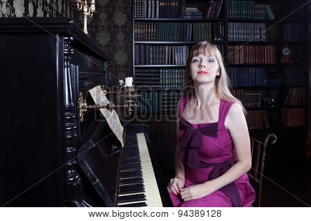 Young Woman Sits At Piano In Room With Bookshelves And Brown Wallpapers