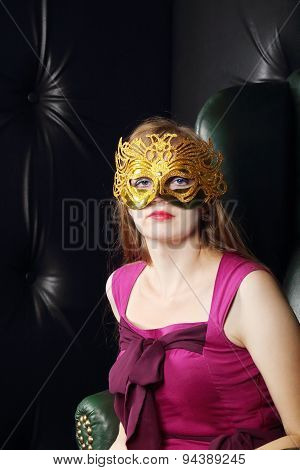 Young Woman In Gilt Mask Sits In Leather Armchair In Room With Leather Wall