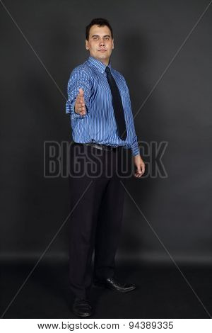 Handsome Man In Tie And Blue Shirt Stands In Black Studio And Offers Handshake