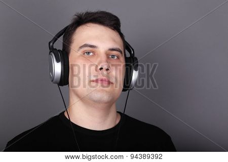 Beautiful Young Man In Headphones And Black T-shirt In Grey Studio