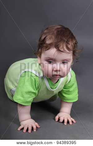 Handsome Little Baby Boy In Green Crawls On Floor In Grey Studio