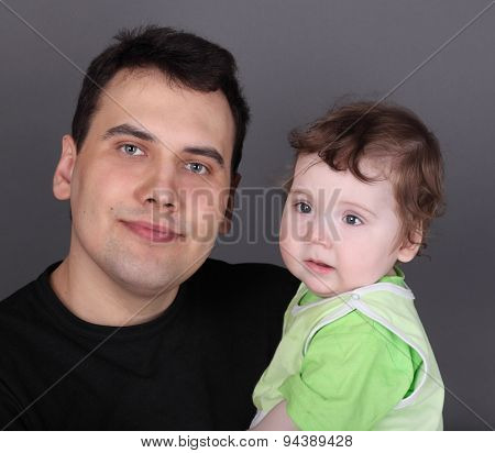 Happy Handsome Father Holds His Little Baby Son In Green In Grey Studio