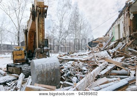 Excavator Demolition Log Wooden House In Snowfall On Winter Day