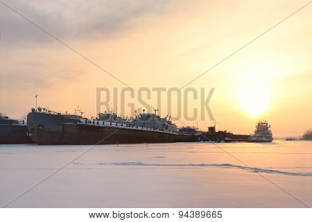 Big Rusty Ship In Frozen River In Evening Winter Evening At Sunset