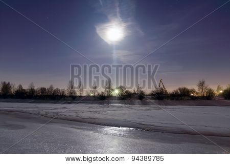 Frozen River Covered With Ice Reflects Light From Moon At Night And Beautiful Sky