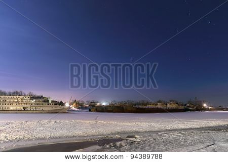Passenger Ships In Frozen River Covered With Snow At Night And Beautiful Starry Sky
