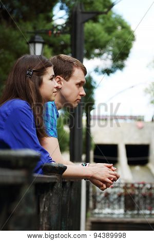 Young Man And Woman Stands Near Railing Near Small River In Park At Summer Day And Look Away