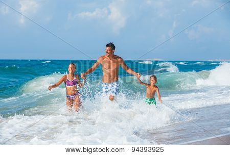 Father and children playing on the beach