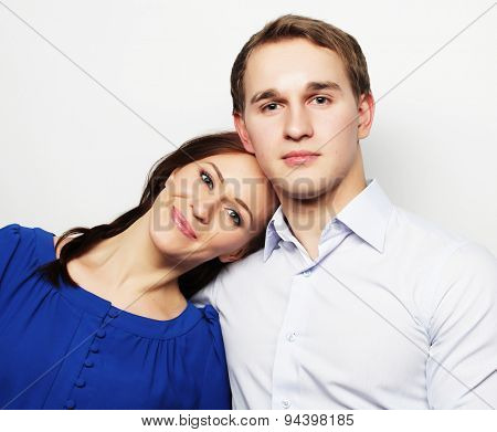 Love, family and people concept: lovely happy couple hugging over grey background.