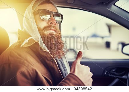 hipster with beard sitting in car giving thumbs up, shot with lens flare, retro filter and selective focus