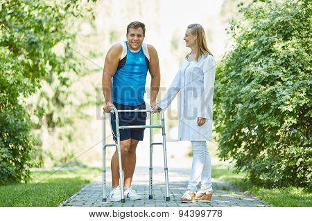 Female clinician and young man with walker taking walk in park
