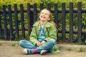stock photo of schoolgirls  - Little laughing schoolgirl  sitting on the street with her backpack - JPG