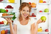 stock photo of refrigerator  - Woman on a diet to choose between healthy and unhealthy food near refrigerator - JPG