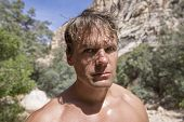 pic of wilder  - Closeup portrait of shirtless Caucasian man with crazy look in his eyes under sunny sky in natural wilderness environment - JPG