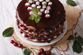 picture of icing  - Big cake with cherries and chocolate icing on a plate close - JPG