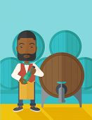 stock photo of inspection  - An african wine maker standing wearing his apron holding a bottle of wine inspecting from barrel inside the wine storage room - JPG