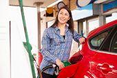 stock photo of petrol  - Woman man refuelling a car at a petrol station - JPG
