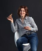 picture of cigar  - middle aged woman with glass of whiskey and cigar on black background  - JPG