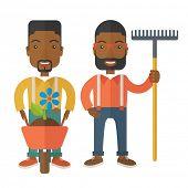 foto of wheelbarrow  - Two black smiling gardener carries a plant in wheelbarrow and holding a rake - JPG