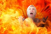 image of upset  - Upset woman screaming with hands up against fire - JPG