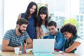 stock photo of gathering  - Happy creative business team gathered around a laptop at office - JPG