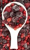 stock photo of berries  - White porcelain bowl with frozen berries stands in the midst of other berry fruits - JPG