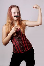 image of crossdressing  - young woman with fake moustache on a stick showing off biceps muscle - JPG