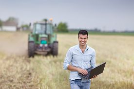 pic of tractor-trailer  - Young attractive businessman with laptop standing in front of tractor with trailers on harvested field - JPG