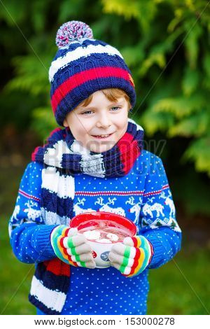 Happy little kid boy drinking hot chocolate drink and marshmallows outdoors on Christmas market. Funny child in winter fashion clothes. On cold winter day during snowfall.