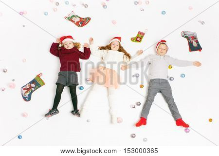 Merry Christmas 2016 Black Friday 2016 Image Cute little kids lying at decorated Cristmas background with white background. Concept of celebrating holiday. Children happy to receive many gift boxes