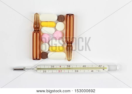 medicinal tablets thermometer and ampoule on a white background