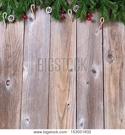 Wooden background for Christmas concept with fir branches candy canes and red berries. Overhead view with copy space.