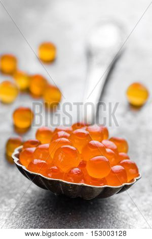 red caviar in spoon on dark background