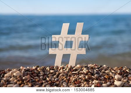 White paper figurines of letters on a sandbeach